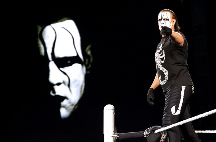 Sting poses on the corner turnbuckle as he points into the camera