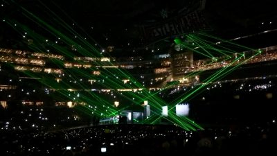 Fluorescent green lasers bounce around the AT&T stadium as Triple H makes his entrance.