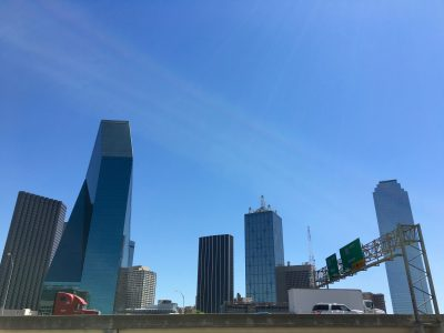 Blues skies shine as a backdrop to the cityscape of Dallas and passing traffic in the foreground on a busy highway.